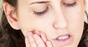 woman having toothache at home